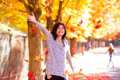 Teen girl throwing colorful autumn leaves in air under trees Royalty Free Stock Images
