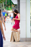 Biracial teen in red dress outside stores with shopping bags Stock Photo