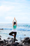 Biracial teen standing on rock by ocean doing yoga Royalty Free Stock Images