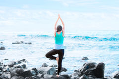 Biracial teen standing on rock by ocean doing yoga Royalty Free Stock Photography