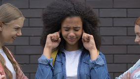 Biracial teenage girl covering ears from bullying, mockery of classmates, racism. Stock footage stock video footage