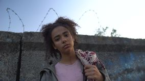 Biracial teenage girl holding bag, dreaming to escape from refugee camp, poverty. Stock footage stock video footage