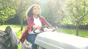 Biracial teenage girl young woman driving a gray tractor through a sunny apple orchard