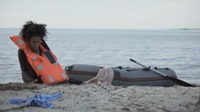 Biracial teenager in life jacket getting out of boat, survived flood, disaster. Stock footage stock video