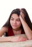 Biracial tonårig flicka i den röda klänningen som ser borrad eller tröttad och att luta Royaltyfri Fotografi