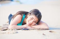 Biracial tonårig flicka som ligger på den sandiga stranden, att vila och att le Arkivbild