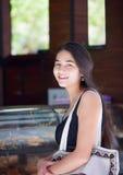 Biracial tonårig flicka som väntar i linje på kaféräknaren Arkivfoton