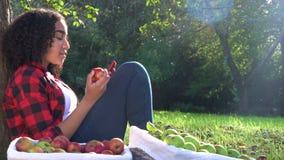 Biracial ung kvinna för tonårs- flicka som sitter mot ett träd som äter ett äpple genom att använda hennes smarta telefon för mob lager videofilmer