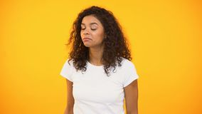 Biracial woman announcing shop discounts, calling for friend, yellow background. Stock footage stock video