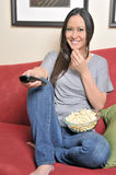 Biracial woman eating popcorn watching TV Royalty Free Stock Photography