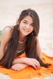 Biracial yeen a la muchacha que miente en la manta anaranjada en la playa Fotografía de archivo libre de regalías