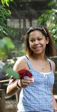 Biracial young woman. Feeding a small bird by hand Royalty Free Stock Photography