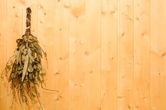 The birch broom hangs in a sauna or bath on a wooden wall. Rest and relaxation in the spa to keep warm in the cold. The birch broom hangs in a sauna or bath on a stock photography