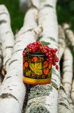 Birch logs and decorative wooden pot in Khokhloma style, overfilled by bunches of ripe red currant. The currant is one of the most widespread berry shrubs of Stock Image