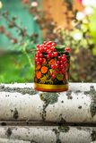Birch logs and decorative wooden pot in Khokhloma style, overfilled by bunches of ripe red currant. The currant is one of the most widespread berry shrubs of Royalty Free Stock Photos