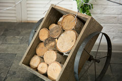Birch logs in a wooden cart with iron wheels Stock Photos