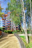 Birch trees and Modern glass apartment residential building. And outdoor facilities Royalty Free Stock Photography