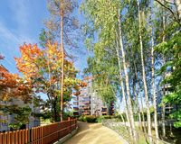 Birch trees and Modern glass residential apartment building. And outdoor facilities Royalty Free Stock Photo