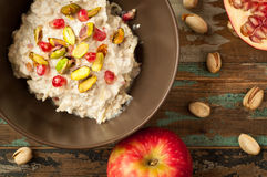 Bircher Muesli. Home made bircher muesli with pomegranate, pistachio, and apple. Served on a rustic wooden table with a scattering of nuts and fruit Stock Image