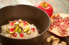 Bircher Muesli. Home made Swiss style bircher muesli with added pomegranate, apple and pistachio nuts Royalty Free Stock Images