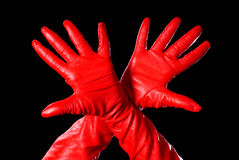 Bird. Hands in red gloves on the black background showing bird's wings Royalty Free Stock Photography
