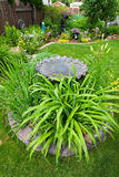 Bird Bath Garden Feature. A gorgeous backyard garden, featuring a center bed of perennials around a bird bath Stock Images