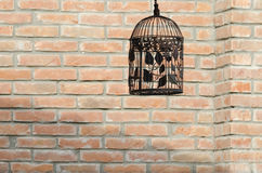 Bird cage. Old fashion bird cage against the orange brick wall Royalty Free Stock Photography