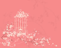 Bird cage among blossom flowers and tree branches Royalty Free Stock Image