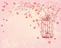 Bird cage among hearts, pink flowers and tree branches Royalty Free Stock Photo