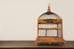 Bird cage on wooden shelf Royalty Free Stock Photos
