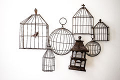 Bird cages hanging on the wall. Bird cages hanging on a concrete wall Stock Photo