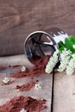 Bird cherry flour with sifter on wooden table. Bird cherry flour with stainless steel sifter on old wooden table with  bird cherry blossoms Stock Image
