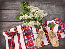 Bird-cherry tree flowers and sandals made of bark Stock Photo
