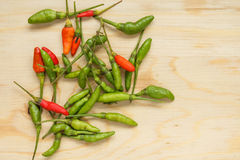 Bird Chilli. Small red and green chilli on wood chopping block Stock Photo
