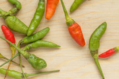 Bird Chilli. Small red and green chilli on wood chopping block Royalty Free Stock Photo