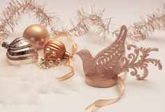 Bird and Christmas balls. Golden Christmas decorations on white background Stock Photos