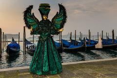Bird costumed masked woman. In front of gondolas in Venice at sunrise Royalty Free Stock Images