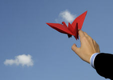 Origami bird in hand against sky Royalty Free Stock Photos