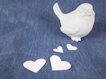 Bird doll and hearts. A bird doll and paper hearts on denim fabric Stock Photos