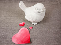 Bird doll and hearts. White bird doll and red painted paper hearts on grey  fabric Stock Photography