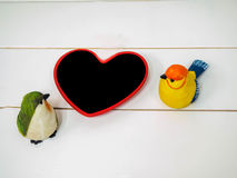 Bird dolls made of stucco on white chair background with small board heart. Black space for insert text or image Stock Images