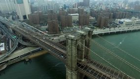 Bird eye view of car traffic on Brooklyn bridge and boat floating under it stock video footage