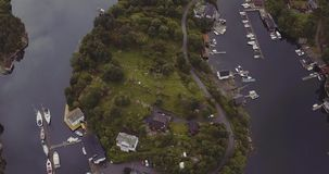 Bird eye flight over island in fjord with yachts houses road stock footage
