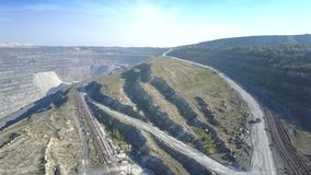 Bird eye flight over rail and ground roads on asbestos pit. Impressive aerial picture railroads and ground roads with truck on asbestos quarry by forestry hill stock video footage