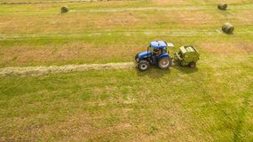 Bird eye of Man at work on the tractor with hay baler royalty free stock photos