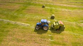 Bird eye of Man at work on the tractor with hay baler royalty free stock image