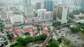 Bird eye time lapse view of railways across road against city landscape. Kuala Lumpur, Malaysia. Bird eye time lapse view of railways crossing road against city stock video footage