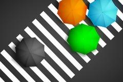 Bird eye view of colorful umbrella and black umbrella on a pedestrian crosswalk. Stock Photo