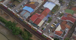 Bird eye view of poor district and riding train on railways. Kuala Lumpur, Malaysia. Overhead view of railways and multicolor train riding throw the slum stock footage