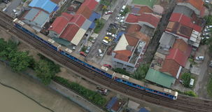 Bird eye view of poor district and riding train on railways. Kuala Lumpur, Malaysia. Overhead view of railways and train riding throw the slum district with poor stock video footage